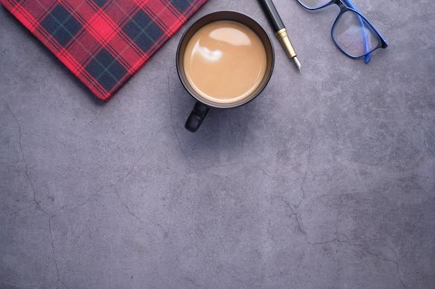 Плоский состав кофе, блокнот и очки на черном фоне.
