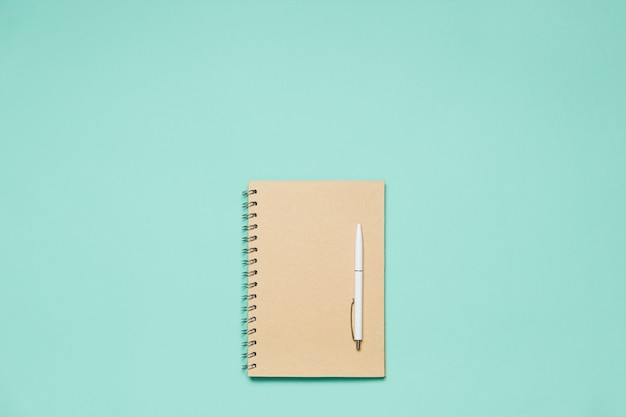 Flat composition notepad with pen on mint desk
