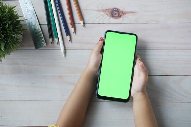 Плоский состав детской девочки, использующей смартфон на столе