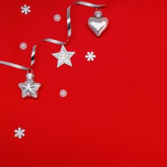 Плоский состав рождественских украшений в серебре на красном фоне.