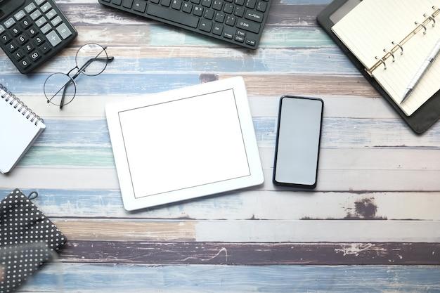 黒の背景に静止したデジタルタブレットとオフィスのフラットな構成。