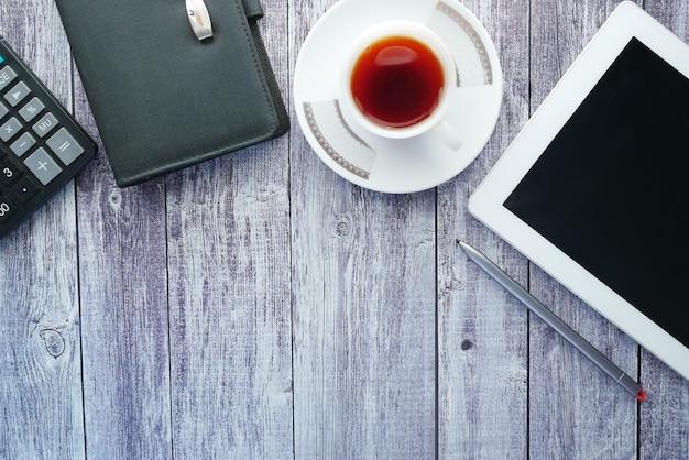 Плоский состав цифрового планшета и стационарного офиса на черной поверхности