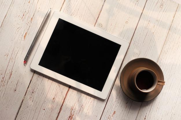 Плоский состав цифрового планшета и чая на деревянных фоне.
