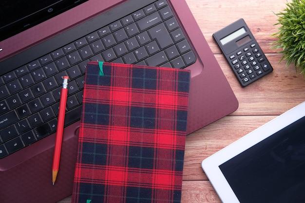 Плоский состав ноутбука и офиса на деревянном столе.