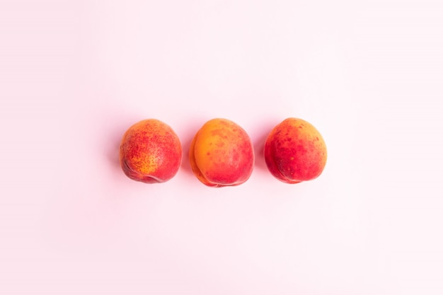 Flat composition  ripe tasty peaches with red side on a pink background.