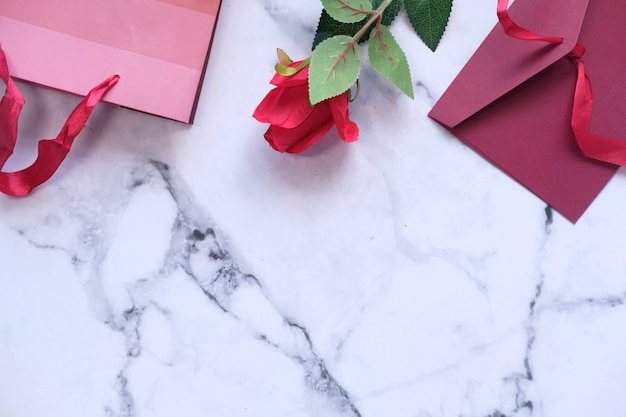 Flat composition of rose, envelope and gift on tile background
