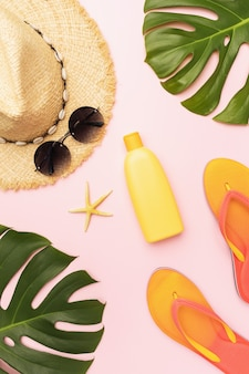 Flat composition with beach holiday accessories and monstera leaves on pink background