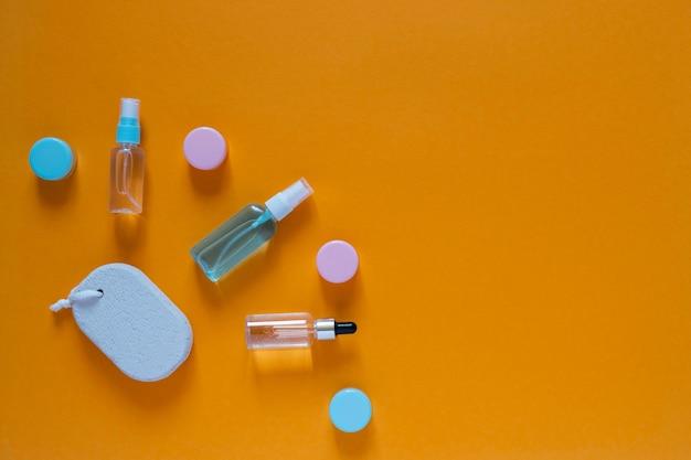 オレンジ色の背景に化粧品を使用したフラットな構成。色とりどりのスポンジ。女性のセルフケア。コピースペースのある上面画像。