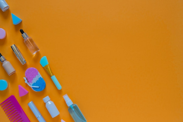 Flat composition with cosmetic products on an orange background. multicolored sponges. women's self-care. top view image with copy space.