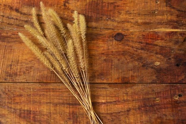 Плоский состав с колосками пшеницы на деревянном столе. уютная осень или концепция зимнего отдыха. место для текста, рамки, вида сверху, пространства для копирования, макета