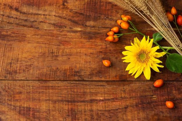 Плоская композиция с колосками пшеницы, ягодами шиповника и подсолнечником на деревянном столе