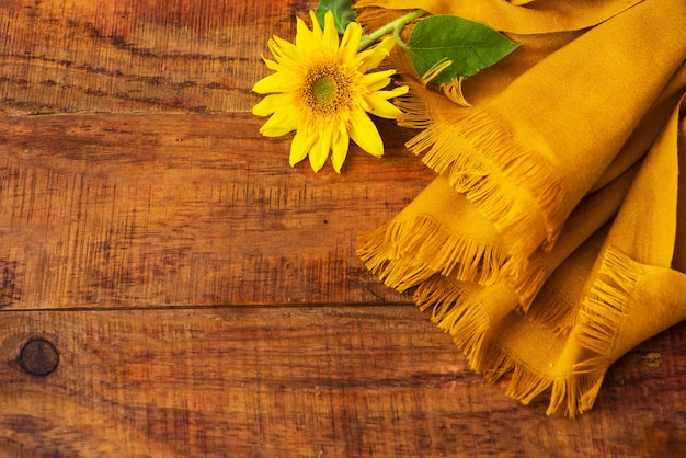 Flat composition with yellow knitted scarf and sunflower on a wooden table. cozy autumn or the concept of winter rest