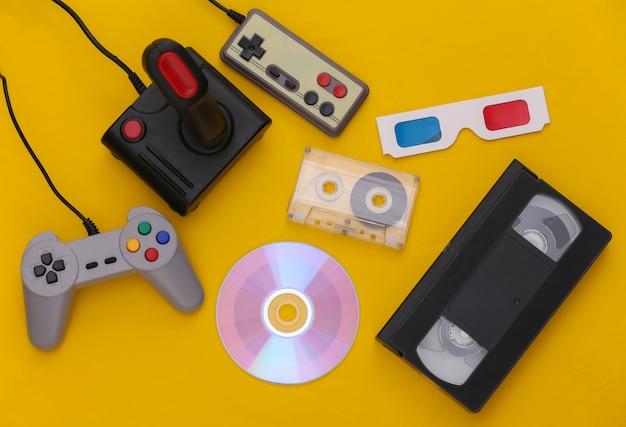 플랫 레이 80년대 속성 구성. 게임 패드, 오디오 및 비디오 테이프, cd, 3d 안경. 레트로 전자 제품, 가제트 및 장치. 엔터테인먼트 및 게임. 노란색 배경입니다. 평면도