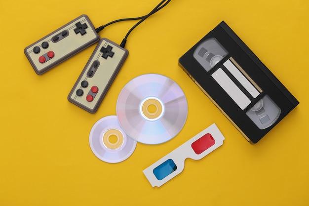 플랫 레이 80년대 속성 구성. 게임패드, 비디오 카세트, cd, 3d 안경. 레트로 전자 제품, 가제트 및 장치. 엔터테인먼트 및 게임. 노란색 배경입니다. 평면도