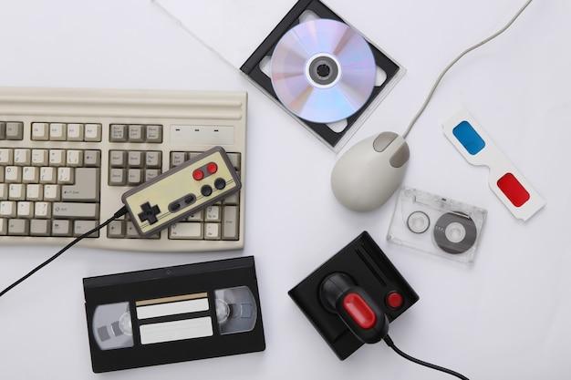 플랫 레이 80년대 속성 구성. pc 키보드, 마우스, 게임 패드, 오디오 및 비디오 테이프, cd, 3d 안경. 레트로 전자 제품, 가제트 및 장치. 엔터테인먼트 및 게임. 흰색 배경. 평면도