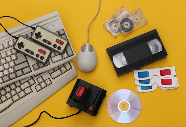 플랫 레이 80년대 속성 구성. pc 키보드, 마우스, 게임 패드, 오디오 및 비디오 테이프, cd, 3d 안경. 레트로 전자 제품, 가제트 및 장치. 엔터테인먼트 및 게임. 노란색 배경입니다. 평면도