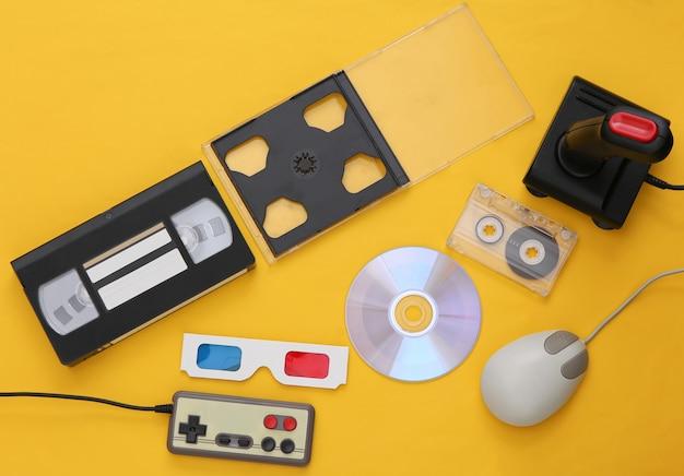 플랫 레이 80년대 속성 구성. pc 마우스, 게임패드, 오디오 및 비디오 테이프, cd, 3d 안경. 레트로 전자 제품, 가제트 및 장치. 엔터테인먼트 및 게임. 노란색 배경입니다. 평면도