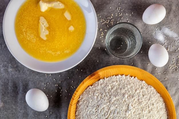 Квартира лежала. набор свежих ингредиентов для приготовления мягкого пушистого теста: сливочное масло, мука, яйцо, стакан воды. процесс приготовления теста для хлеба, кексов, пиццы, булочек и гамбургеров на кухонном столе