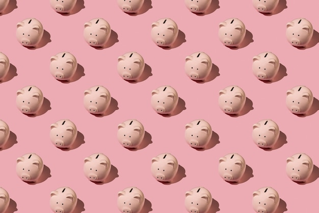 Плоский лежал абстрактный узор с керамической розовой копилкой на розовом фоне. вид сверху. финансы или банковское понятие.