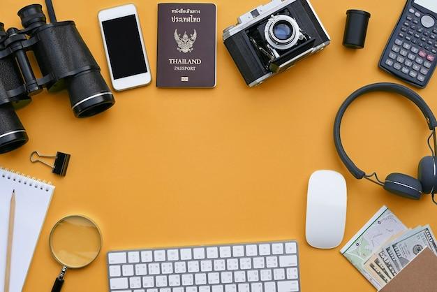 Flat lay of accessories on orange desk