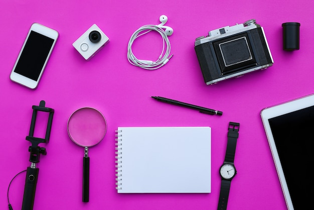 Flat lay of accessories on pink desk background