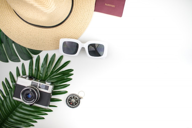 Flat lay accessories for tourists including sunglasses and film cameras on tropical leaves. with copy space for text.