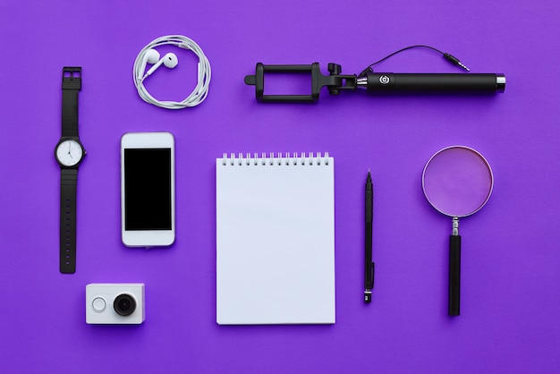 Flat lay of accessories on violet desk background