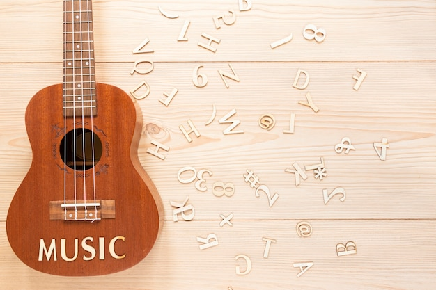 Flat lay acoustic guitar with wooden letters