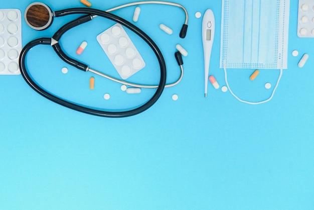 평면 위치 액세서리 의료 및 의료 배경 개념의 공중. 파란색 종이 및 개체에 테이블 상단보기 청진 기.