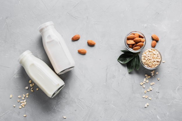 Flat lay almonds and oatmeal with milk bottles