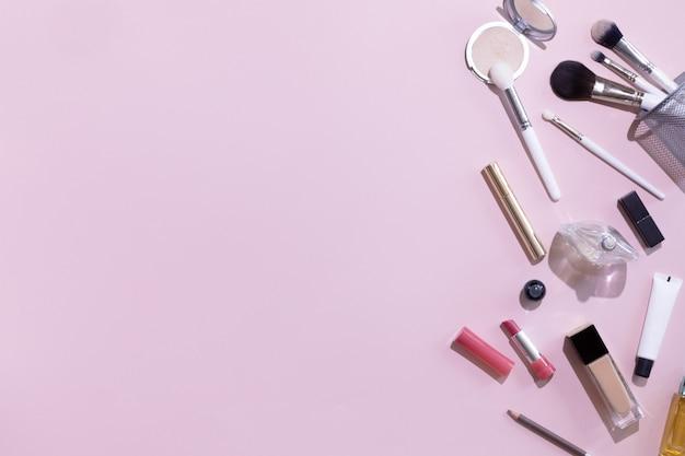 평면 위치 및 메이크업 제품 및 화장품 copyspace와 분홍색 배경에 설정의 상위 뷰. 블로거, 파스텔 여성 비즈니스 사무실 테이블 책상을위한 뷰티 개념