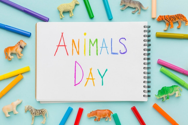 Flat lay of animal figurines and colorful writing on notebook for animal day