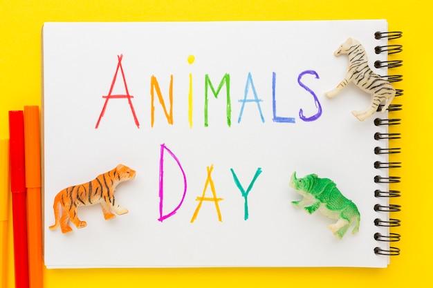 Disposizione piatta di figurine di animali con scritte colorate su notebook per la giornata degli animali