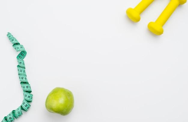 Piatto disteso di mela con metro a nastro e pesi