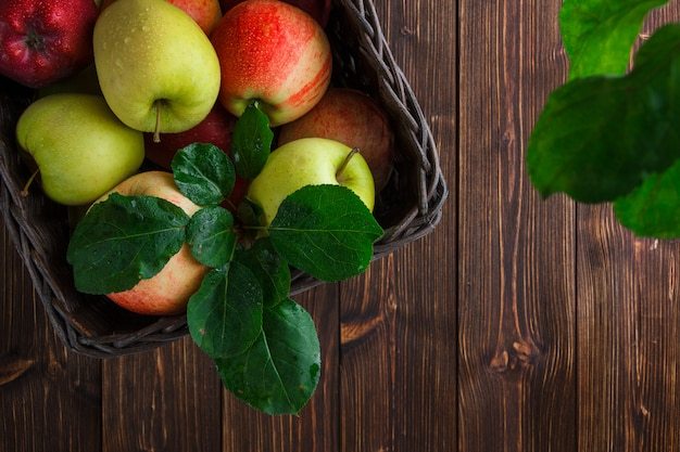 Flat lay apples in box with leaves on wooden background. horizontal space for text
