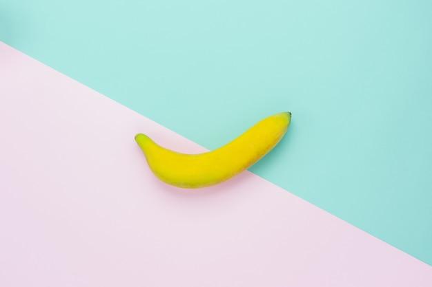 Flat lay of arrangement banana on modern rustic pink & blue paper.