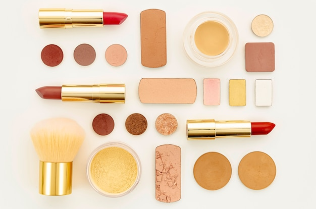 Flat lay arrangement of colorful cosmetics on white background