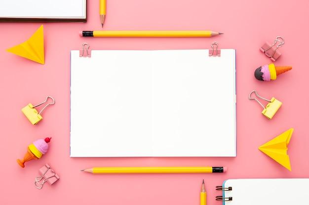 Flat lay arrangement of desk elements on pink background