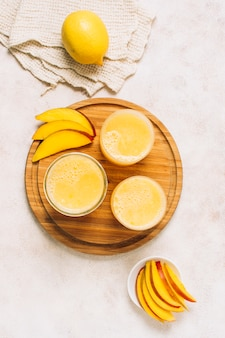 Flat lay arrangement of fresh smoothies next to sliced mango