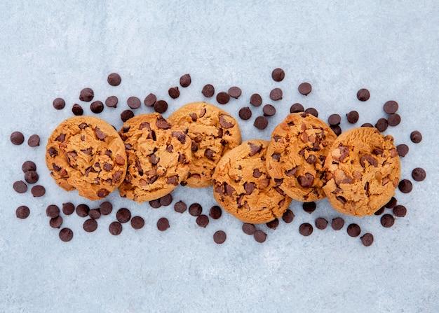 チョコレートチップに囲まれたクッキーのフラットレイ配置