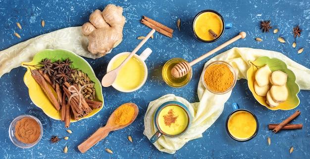 黄金のウコンミルクとその料理の食材のカップのフラットレイアウトの配置。青いテクスチャ背景。