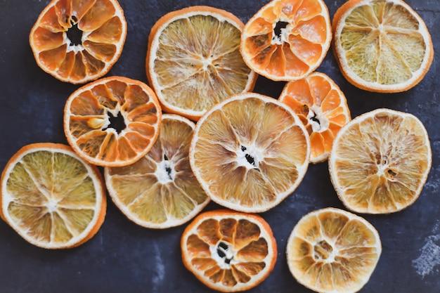 暗い背景の上面図にドライオレンジとマンダリンフードパターンのフラットレイ配置