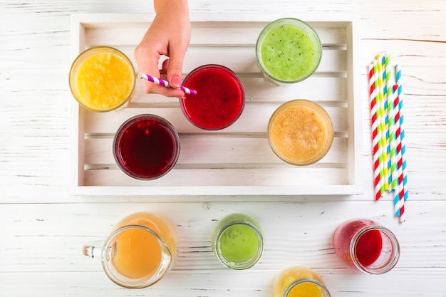Flat lay arrangement of smoothies on wooden tray