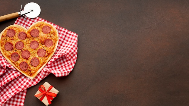Flat lay arrangement for valentines day with heart shaped pizza and copy space