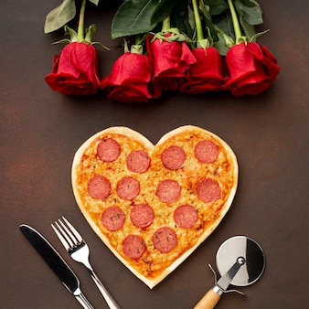 Flat lay arrangement for valentines day with heart shaped pizza