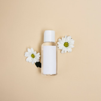 Flat lay arrangement with bottle and daisies