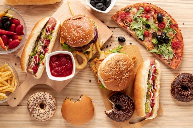 Flat lay arrangement with burgers and pizza