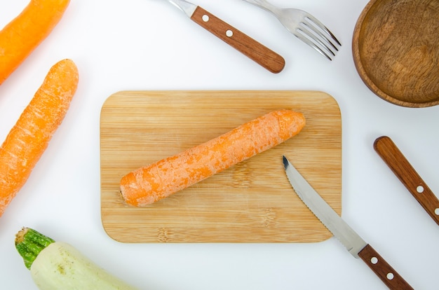 Flat lay arrangement with carrot on cutting board