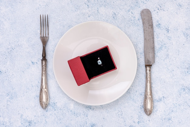 Flat lay arrangement with engagement ring on a plate