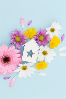 Flat lay arrangement with flowers and wooden house